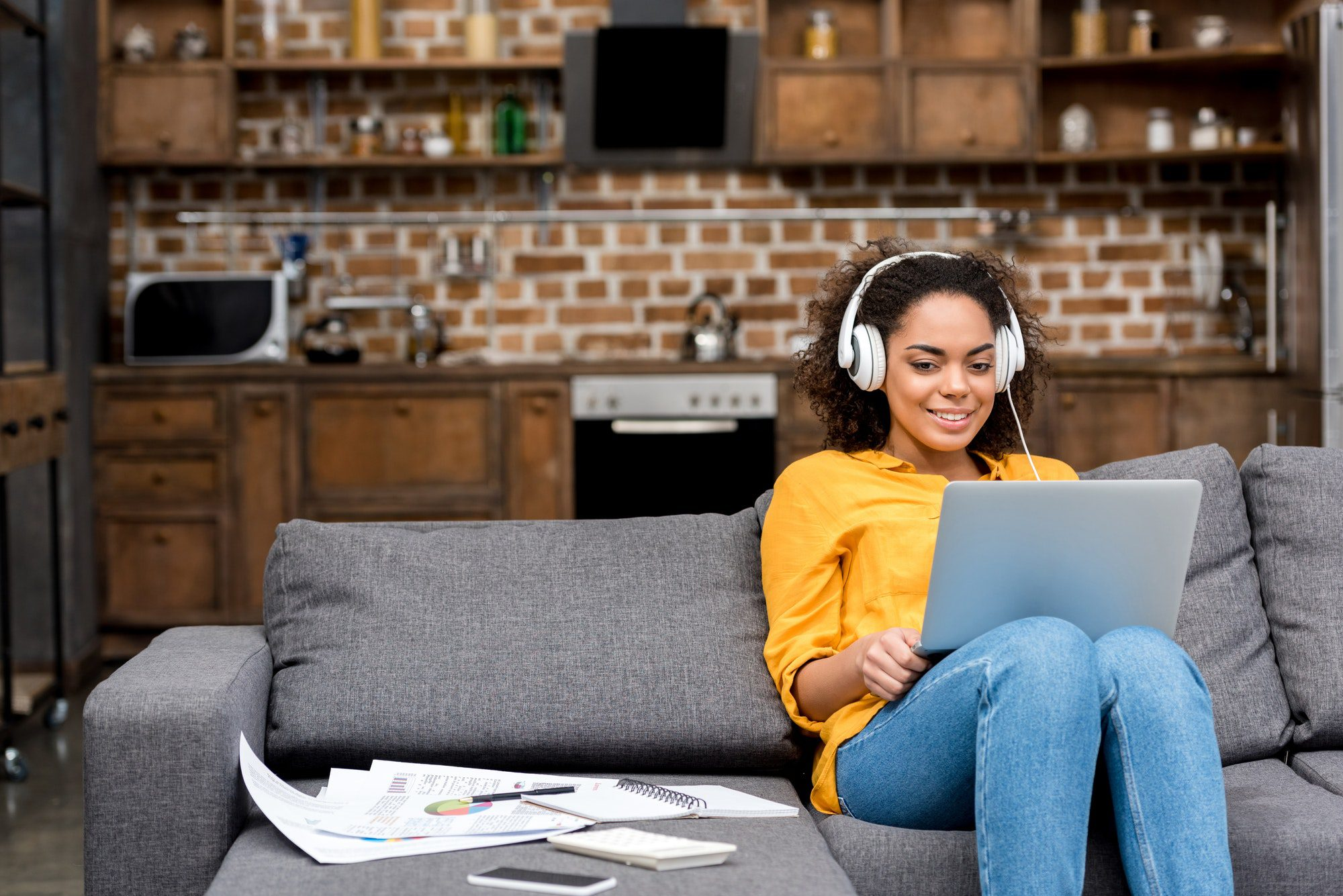 attractive young woman reading EDM News Magazine with laptop and listening EDM music at home